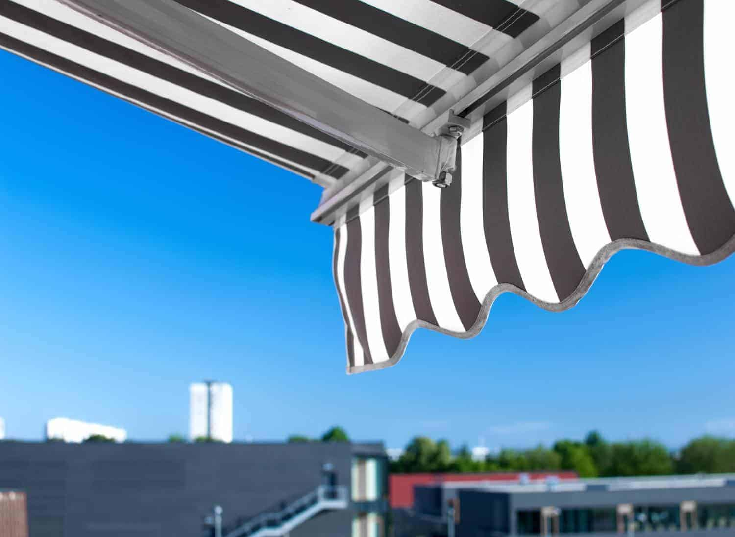 stock-photo-awning-against-blue-sunny-sky-654861580