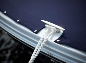 stock photo close up of a chrome boat cleat on the starboard side of a motor boat tied to a white nylon anchor